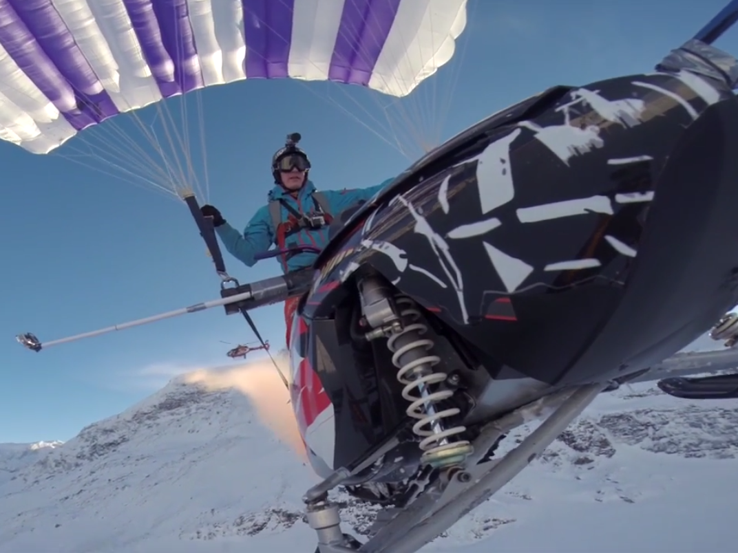 Tying a parachute to a snowmobile and driving it off a mountain may just be too awesome.