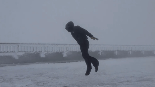 Man struggling to stand against 100+ mph winds on a mountain accidentally learns to fly.