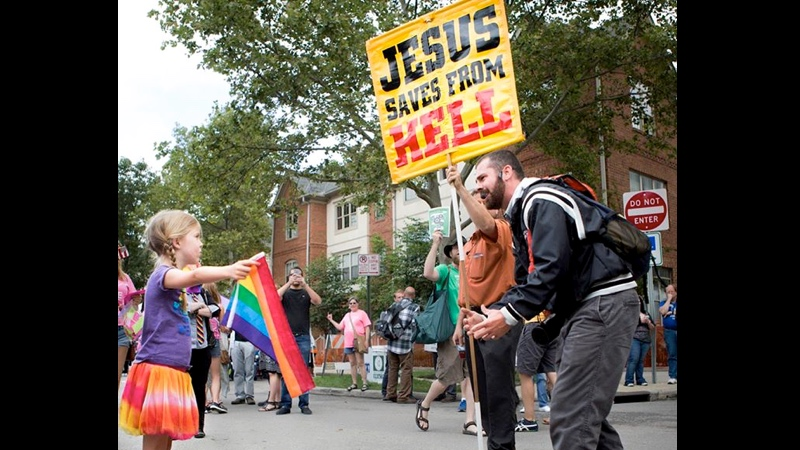 7-year-old girl silently stands up to homophobic street preacher, wins the Internet's heart.