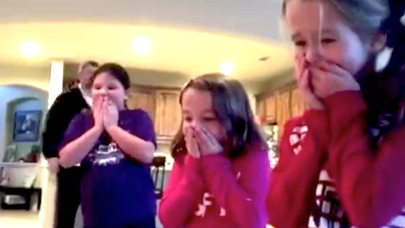 Couple surprises kids by putting their new adopted baby brother under the Christmas tree.
