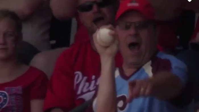 Dad catches foul ball with one hand while holding something very precious in the other.