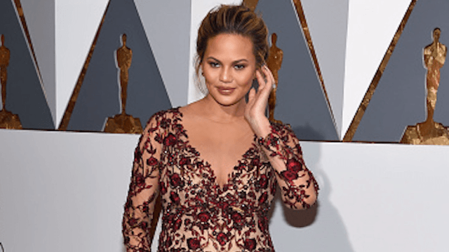 Chrissy Teigen issues hilarious apology for accidentally showing her 'hooha' on the AMA red carpet.