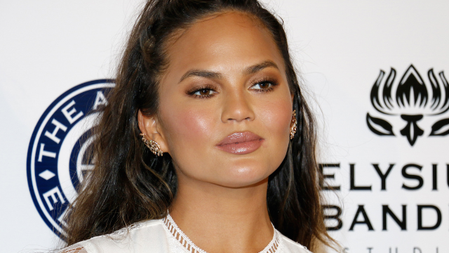 Chrissy Teigen slams fan who made a backhanded comment on her throwback photo.