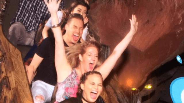 Chrissy Teigen tries to hold onto her milk during an amusement park ride.