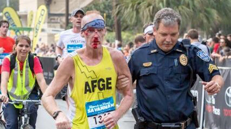 A cop helped a marathon runner make it through the finish line after he took a bloody tumble.