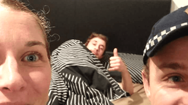 Police officers pose for bizarre bedroom selfie with drunk guy they just took home.