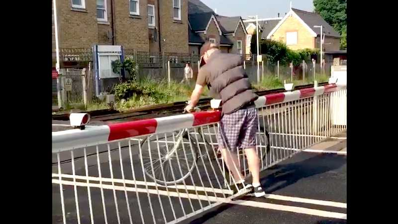 Angry bicyclist demonstrates exactly why you shouldn't climb over a railroad crossing.