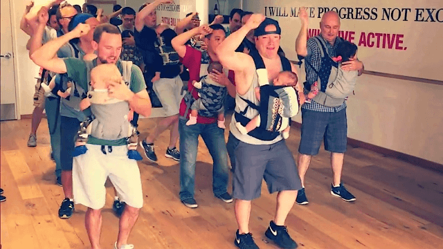 Dads and their dad bods movin' to the groovin' with babies strapped to their chests.