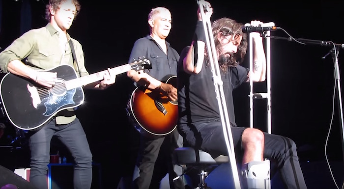 Grohl going hard in crutches and homemade half-jorts. (via YouTube)