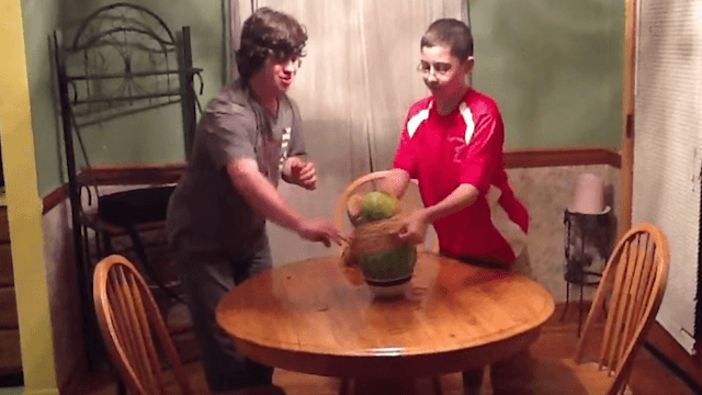 Kids wrap rubber bands around a watermelon to make it explode, still don't see it coming.