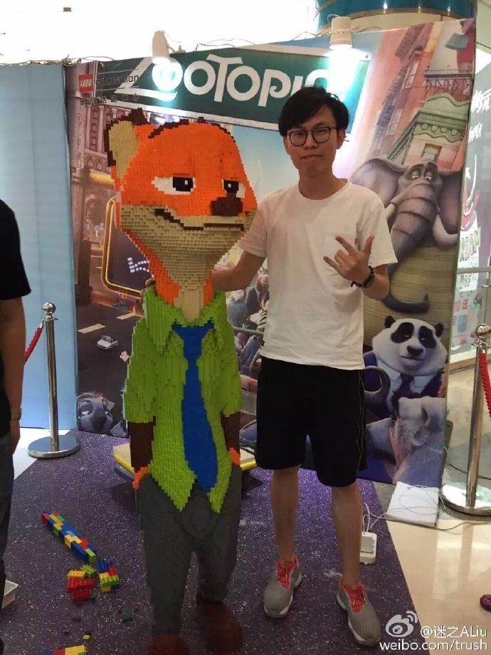 Chinese artist Zhao stands next to his magnificent Lego statue of Nick the fox from Zootopia.