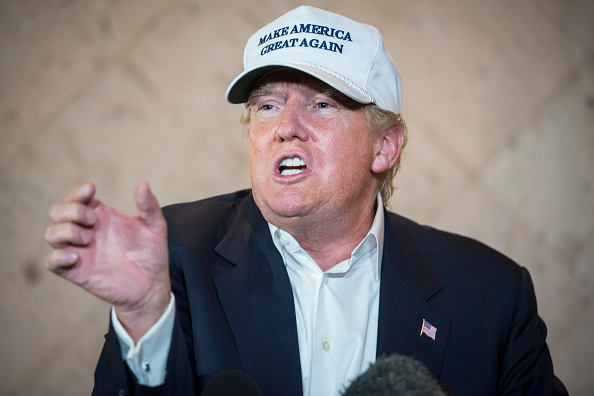 Trump making a lewd gesture in a sweet hat. (via Getty)