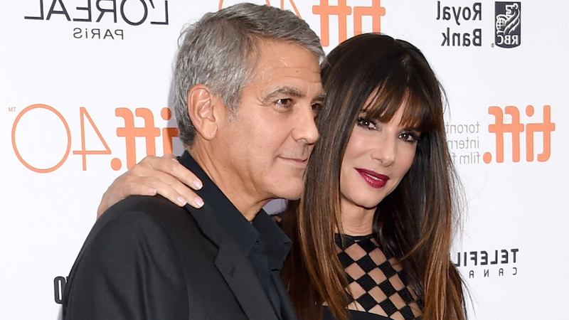 George Clooney accompanying Bullock to accept more awards he could've won.