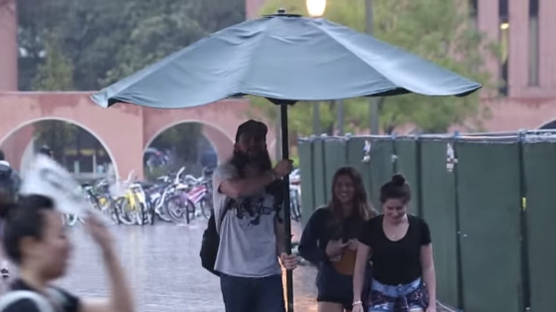 Benevolent prankster brightens rainy day by covering strangers with a giant umbrella.
