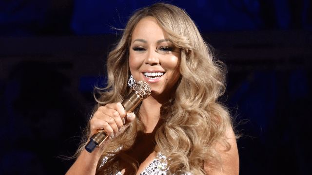 Mariah Carey harnesses Christmas magic to sit in what must be an invisible chair at her concert.