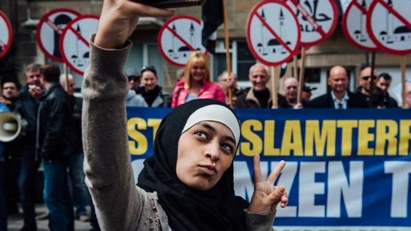 A young Muslim woman protested protesters by taking selfies in front of them.