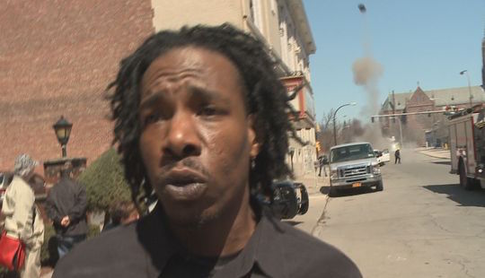 Man being interviewed about underground explosions interrupted by flying 100lb. projectile.