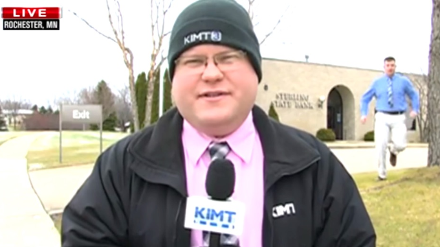Reporter maintains amazing chill when his live broadcast is interrupted by a bank robber.