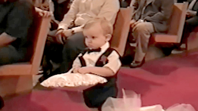 Very cute ring bearer decides he's done delivering the rings a little too soon.