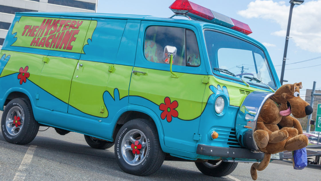 Woman in Scooby Doo 'Mystery Machine' chased by police, not by criminal in ghost mask.