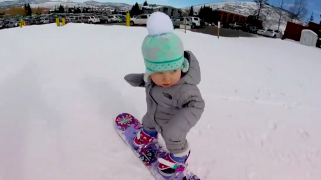 one year old snowboarder has already mastered the moves and the