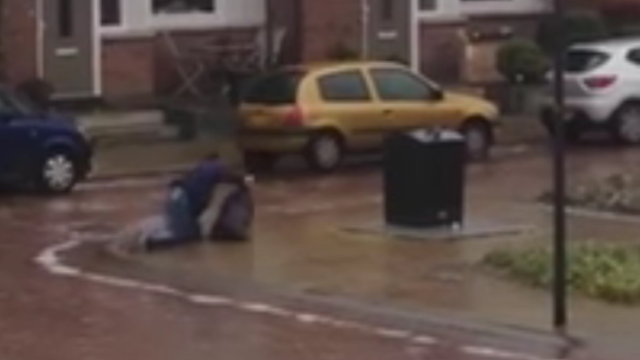 Man struggling valiantly to take out trash on an iced-over street is the Sisyphus of our age.