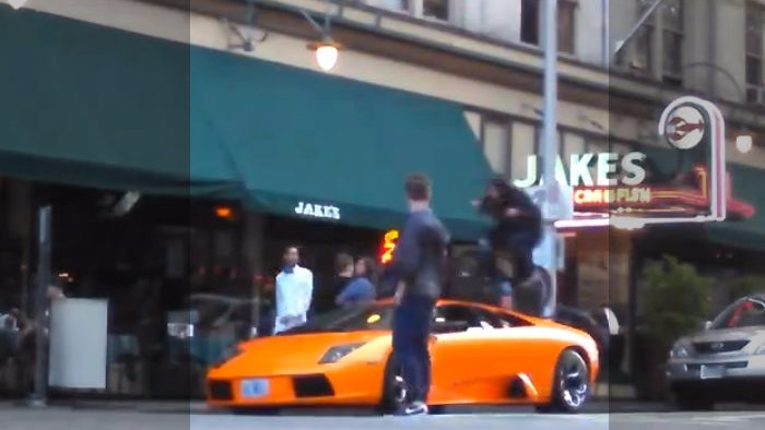A BMX biker did a rude but cool trick on a Lamborghini, but the star was a waiter's reaction.