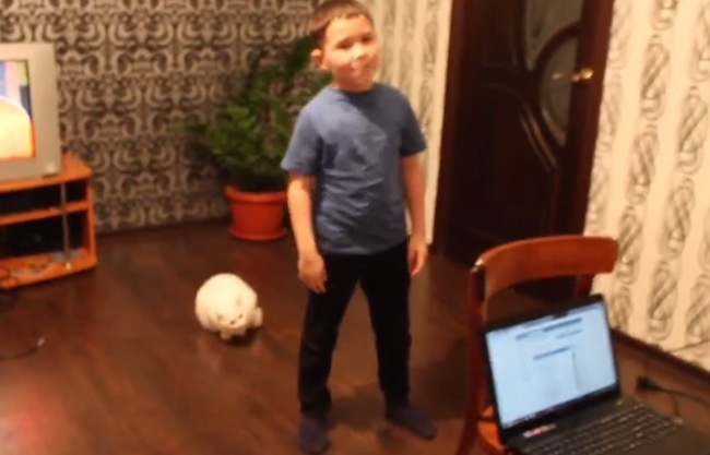 The family cat has had enough of this boy's singing, and brings it to a screeching halt.