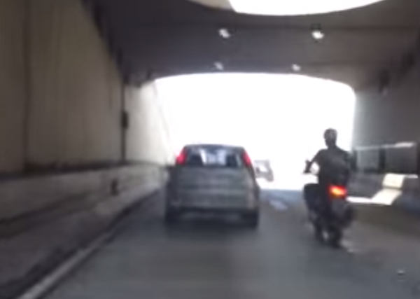 An angry biker found out that kicking a moving car is never a good idea.