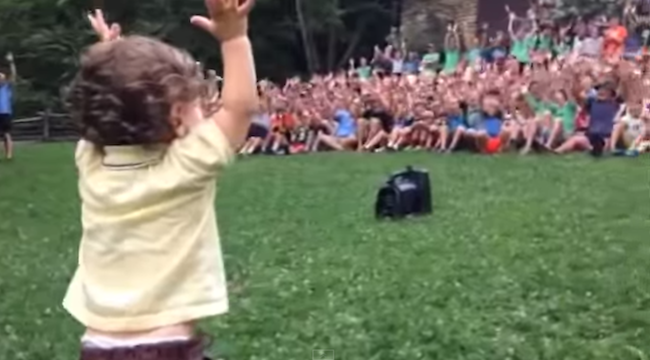A toddler takes control of a crowd of 500 boys at summer camp. Powerfully cute.