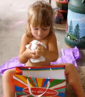 This adorable little girl absolutely loves her jerky mom's intentionally crappy present.