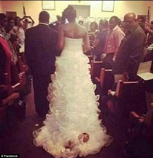 A bride drags her month-old baby down the aisle fastened to the train of her wedding dress.