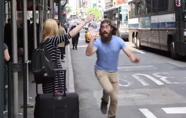 Happy weirdo spreads joy in New York City by high-fiving people waving for cabs.
