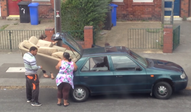 This family's futile attempt to stuff a large sofa into a tiny car is mind boggling.