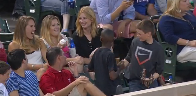 Smoothest kid ever catches foul ball at game, then plays a trick to impress the pretty girl behind him.