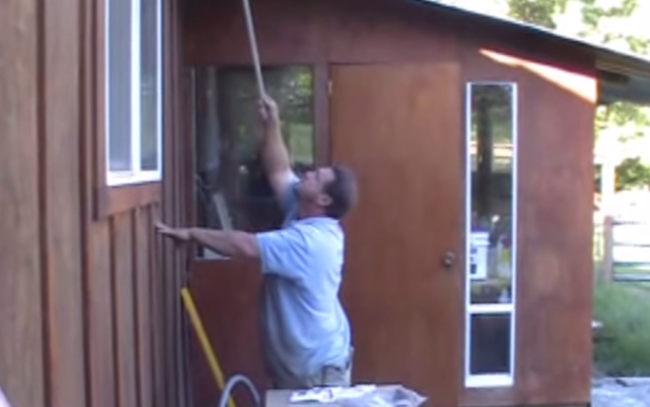 A man loses a battle with a wasp's nest while his wife laughs at him.