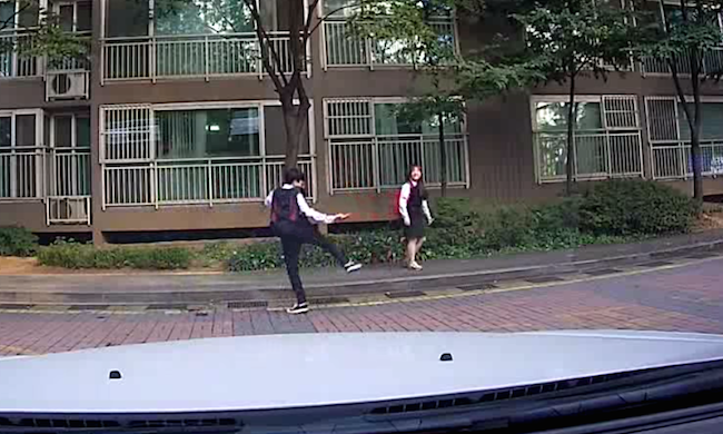 Dash cam captures two teens randomly dancing without a care, and everybody's watching.