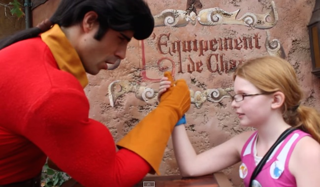 Disney World's Gaston gets burned by a little girl in an arm wrestling contest.