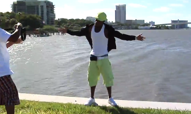 A rapper takes the plunge during a windy photo shoot by the water.
