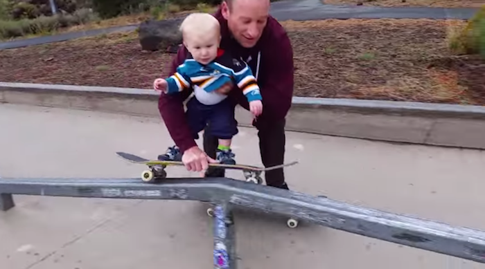 Radical little baby dude grinds out a rail on his skateboard.