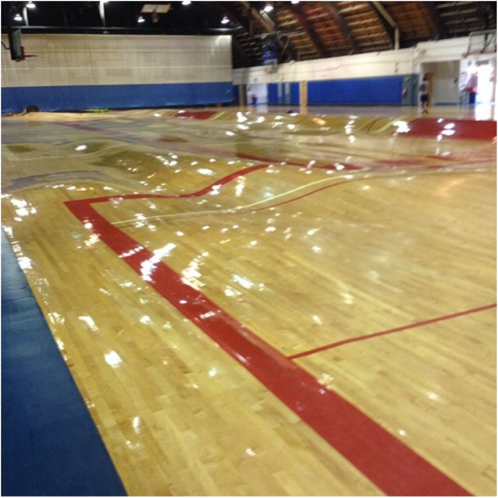 Burst water pipe turns basketball court into a hallucination.