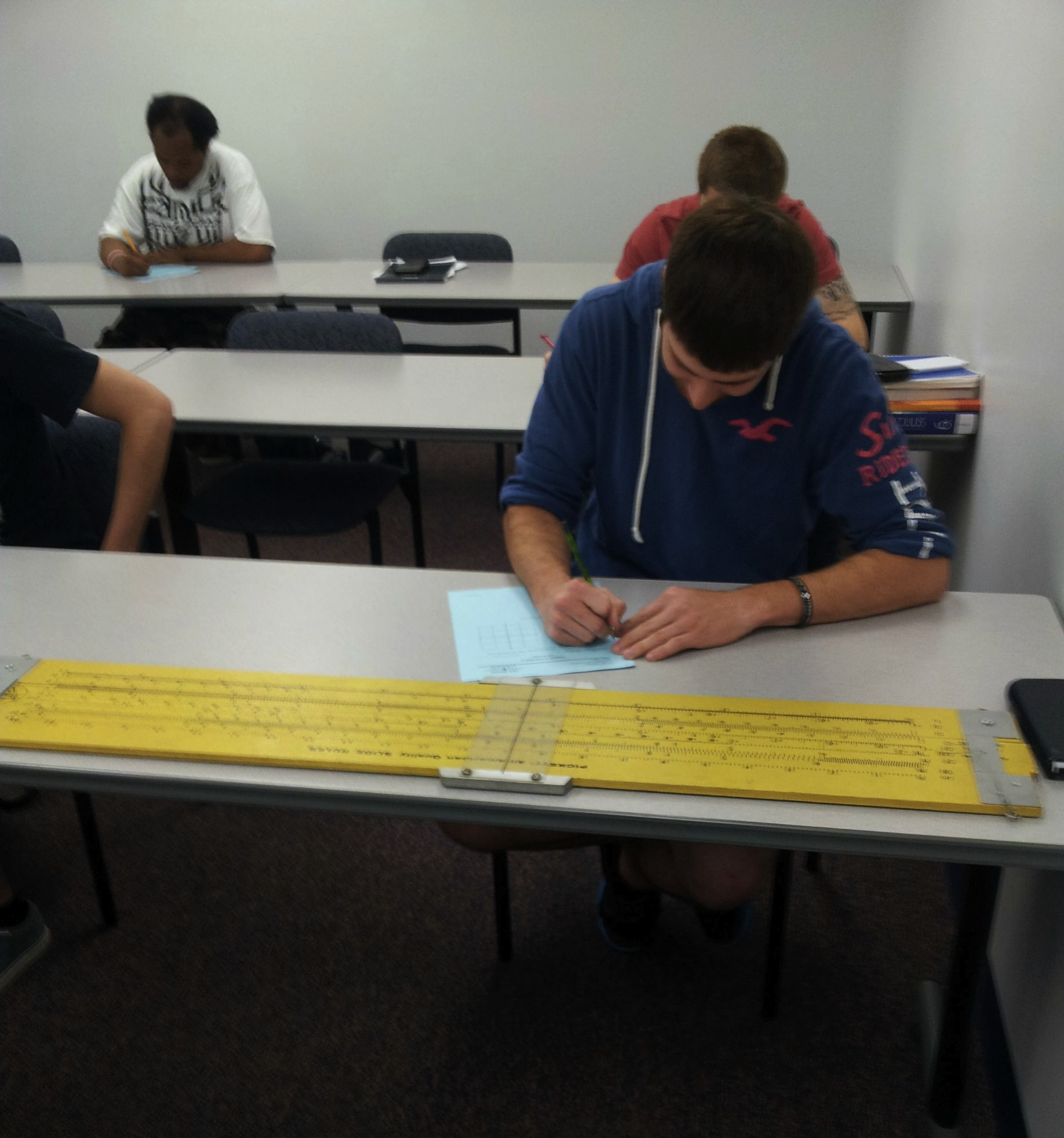 Kid opts to take final math exam without a calculator. Chooses to use 4-ft slide rule instead.