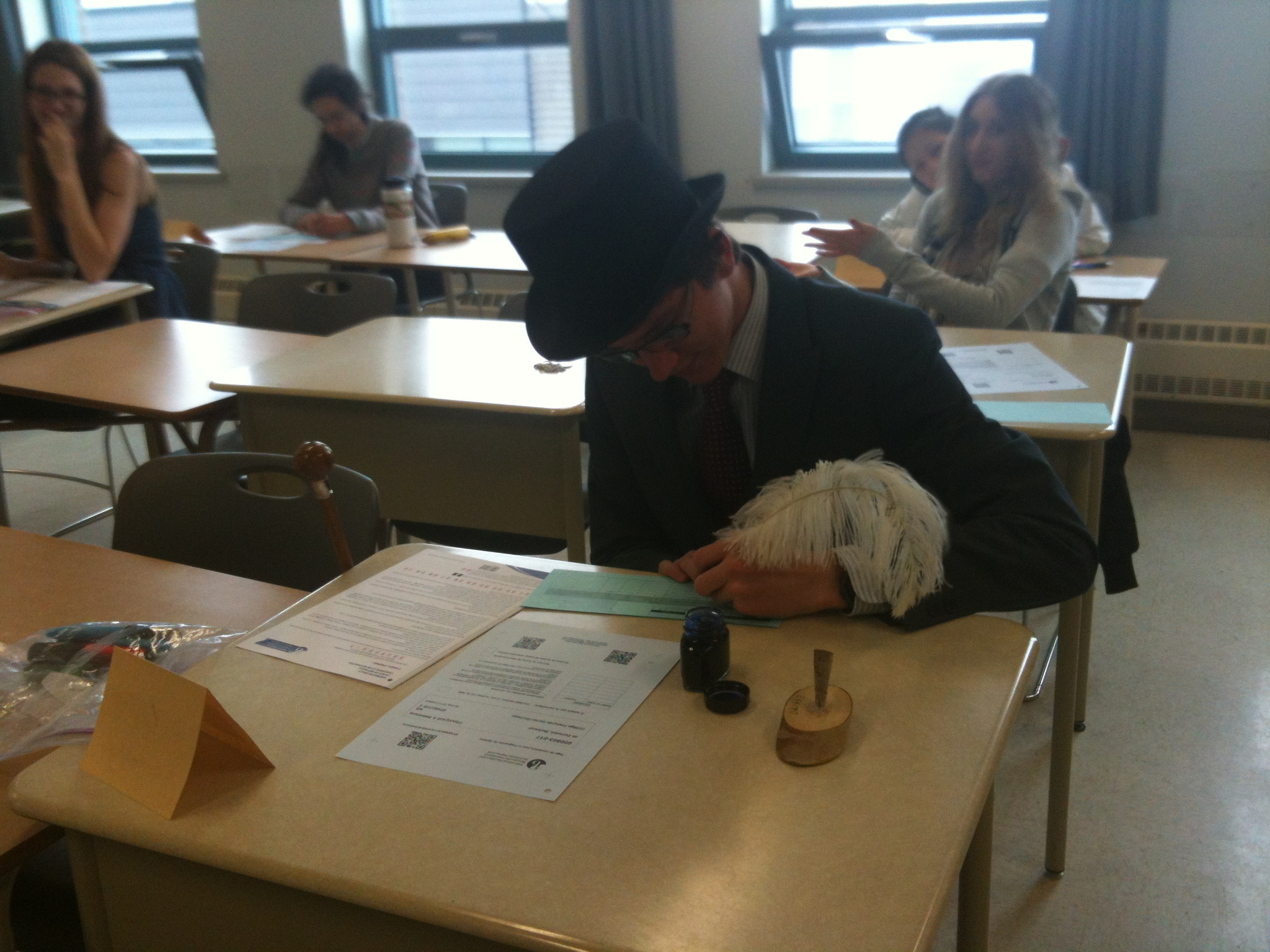 Kid shows up to take his college entrance exams with a suit, top hat, cane, and using a quill pen. We hope he passed.