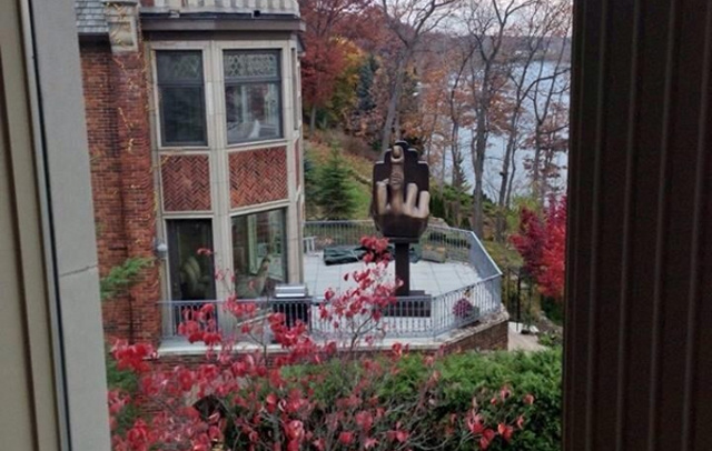 A man bought the house next door to his ex-wife and put up a giant middle finger in his yard.